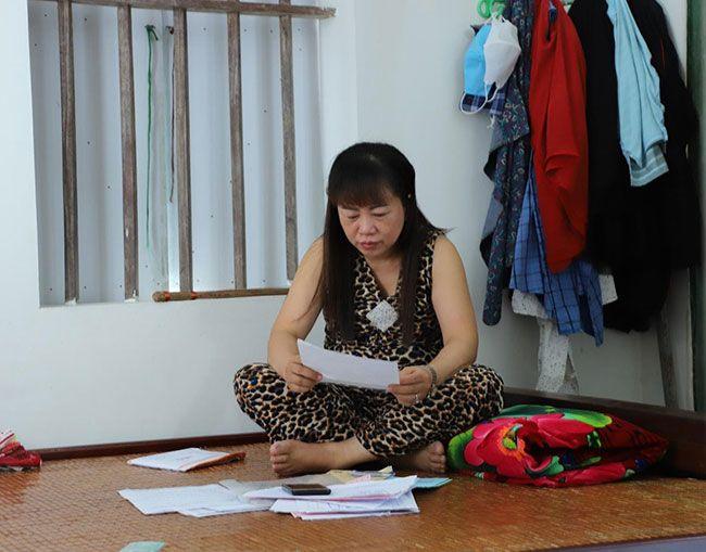 Chị Lụa xúc động khi xem lại hồ sơ bệnh án của mình (Ảnh tác giả cung cấp)